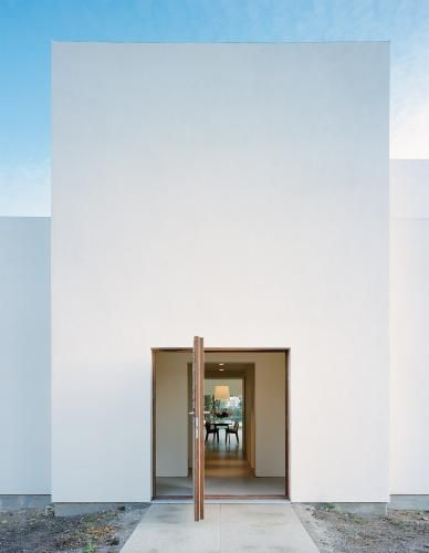 love the oversized pivot door and simple exterior