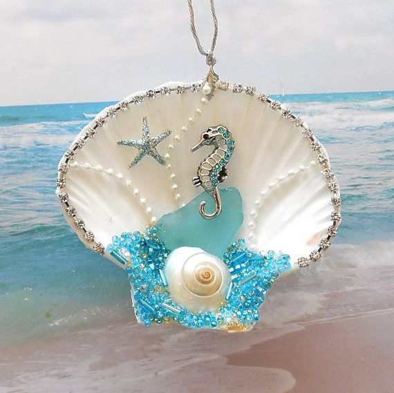 A seahorse ornament unlike any other. Ive taken a beautiful white 3 3/4 inch wide scallop ornament and bedazzled it with aqua and turquoise glass beads, a piece of aqua glass, clear rhinestones, a polished shell and a stunning metallic seahorse covered in sparkling turquoise/aqua glass