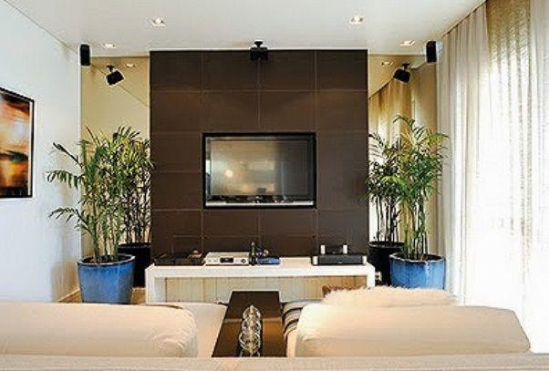 Estante com parede revestida em couro marrom pespontado + espelho bronze nas laterais + móvel baixo em laca branca. Projeto Deborah Roig, via Casa Mix
