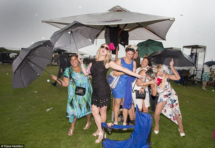 A delightful downpour: The rain did little to dampen the spirits of some punters who embraced the torrential conditions with umbrellas and a smile