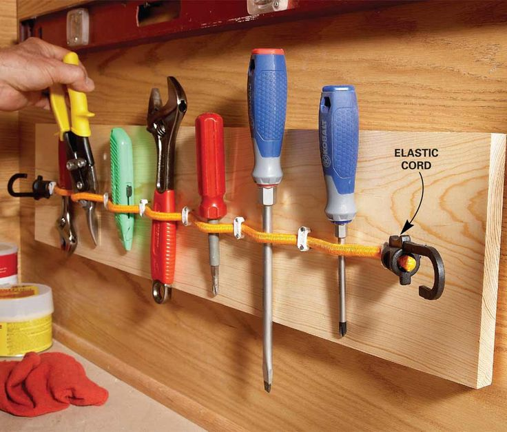 Use elastic cords to make a removable organizer for hand tools. Fasten one end of the cord to a 1x8 using an electrical staple, lay the cord straight without stretching it, then staple the other end. Add staples every 3 in. to create holders, leaving the staples just loose enough so the cord can still move. Then fasten the 1x8 to the wall.