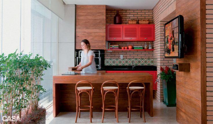 Nesta varanda, assinada pela arquiteta Marina Linhares, o tijolinho aparente se associa aos painéis de madeira de demolição e aos armários vermelhos.