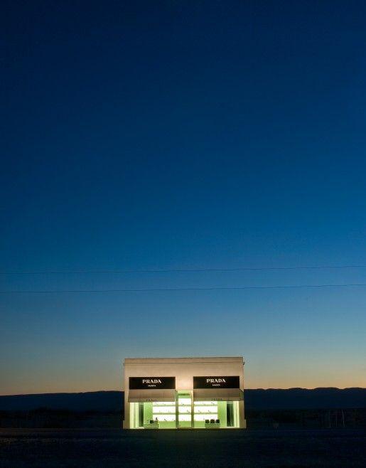 """""""Prada Marfa"""" es un edificio completamente inusual localizado en medio del desierto cerca de Marfa (Texas) en una región desolada atravesada por la autopista 90. Tras el cristal se muestra una selección de zapatos y bolsos, presumiblemente más cara que la propia estructura de la tienda, y que permanece tal y como la dejaron en el 2005."""