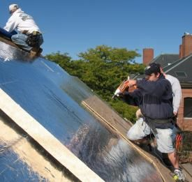 Photo of workers fastening plywood roof sheathing through several layers of rigid foam