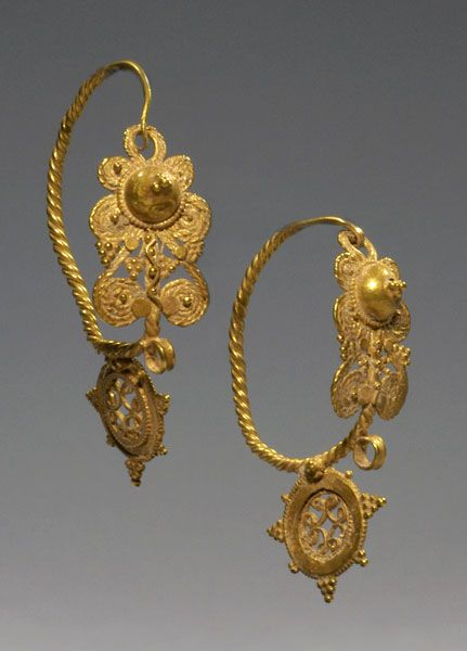 PAIR OF LATE ROMAN OR EARLY BYZANTINE GOLD EAR PENDANTS Central front panel with grape leaves and clusters beneath boss, twisted loop wire and stationary pendant with cruciform design. 5th-6th Century AD