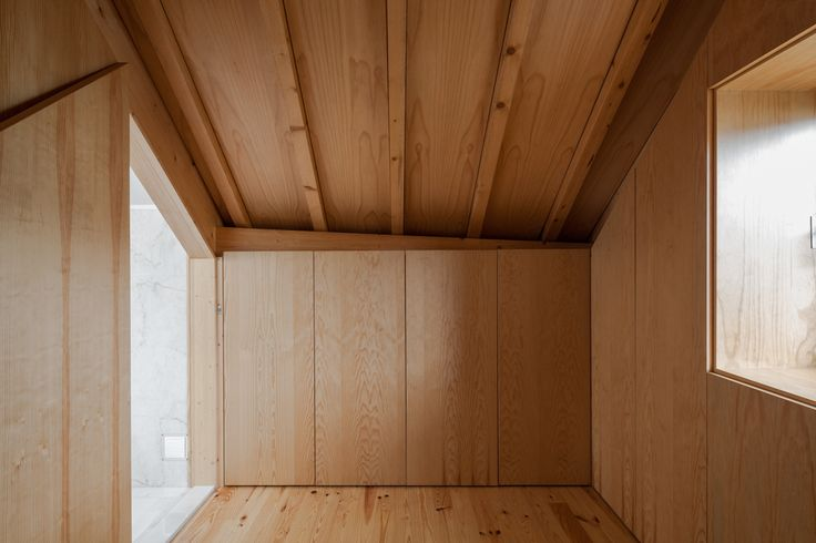 Three Cusps Chalet / Tiago do Vale Arquitectos {detail at panel to window, simple built-in closets against a slope}