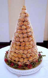 """What is a Croquembouche? A croquembouche or """"piece montee"""" is a wedding cake made from filled choux buns held together with caramel in an impressive pyramid. A very popular choice if there is a French connection within your bridal party and equally popular with the many other couples looking for an unusual, elegant and more interesting option to a traditional British wedding cake."""