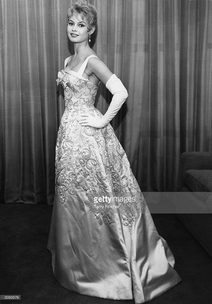 1956: French actress Brigitte Bardot wearing a classical white satin dress embroidered with sequins and pearls at a Royal Film Performance at the Empire in Leicester Square, London.