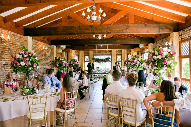The Garden Room dressed for a beautiful wedding | Elegant floral centrepieces and exposed wooden beams | Eschol Park House Wedding venue | Shot by The Moments Chris Photography