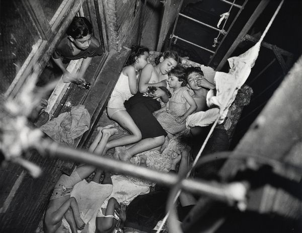 "The hot weather last night took Weegee, the photographer, to the Lower East Side, where he found these children sleeping on a tenement fire escape at Irving and Rivington Streets. Weegee says he gave the kids $2 for ice cream. But their father took charge of the dough. PM Photo by Weegee. ""Heat Spell"", May 23, 1941"