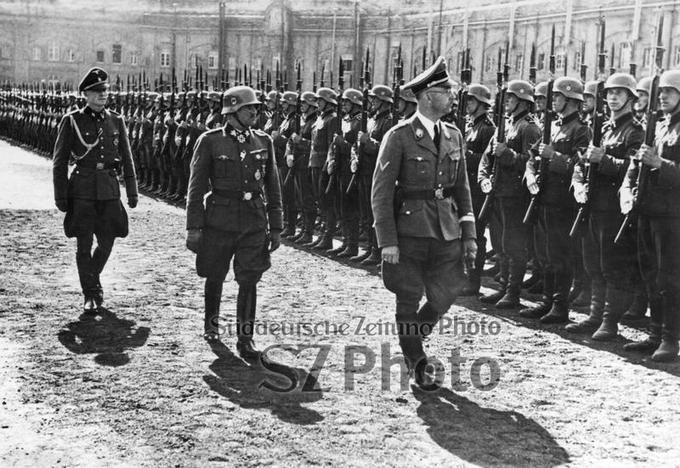 Heinrich Himmler, Sepp Dietrich, Peiper Scherl/Süddeutsche Zeitung Photo. Reichsführer-SS Heinrich Himmler (rechts), der Kommandeur der Leibstandarte SS Adolf Hitler (zweiter von rechts) und der erste Adjutant Himmlers Hauptsturmführer Joachim Peiper (links) schreiten die Front der angetretenen LSSAH ab. Der LSSAH wurde ein neues Feldzeichen verliehen.