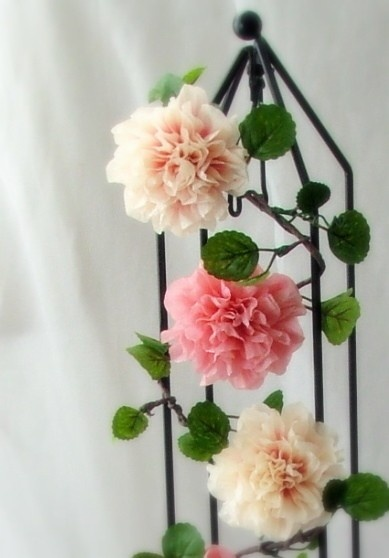 Each garland is made up of 5 hand painted and crafted crepe paper flowers. This gives each flower a realistic look. They are then arranged on a vine, which is made out of hand twisted crepe paper wire. Silk leaves are then arranged on the vines using the same technique.