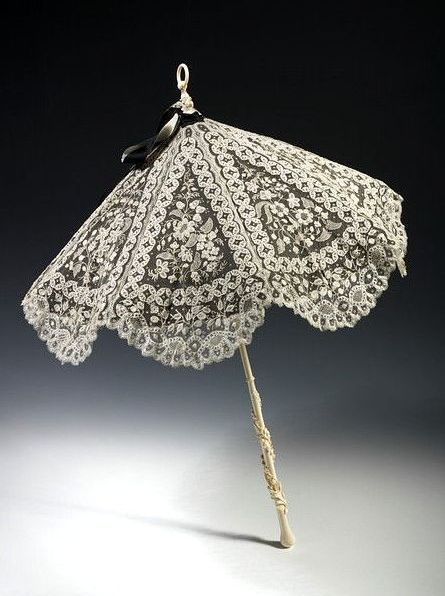 A parasol from the 1870s made of white lace over black silk with a carved elephant tusk ivory handle. The parasol was a popular accessory throughout the 19th century and was used to protect ladies from the effects of the sun at a period when pale skin was the height of fashion. - 1870s fashion