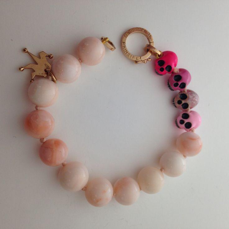 bracciale corallo 'pelle d'angelo' con chiusura e logo in oro rosa, teschi in argento smalto a freddo degrade'.