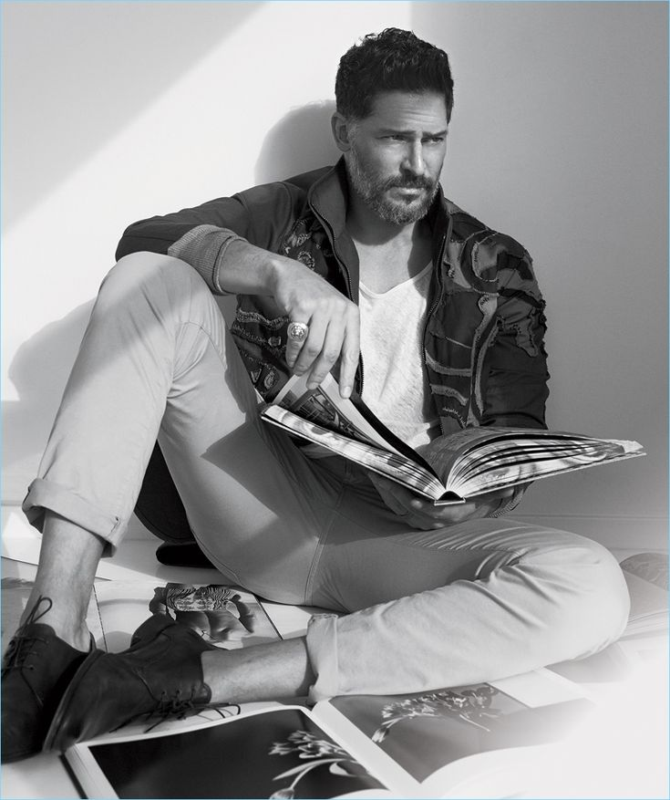 Flipping through art books, Joe Manganiello wears a camouflage Valentino jacket with a t-shirt and shoes by John Varvatos. Manganiello also sports Bottega Veneta jeans.