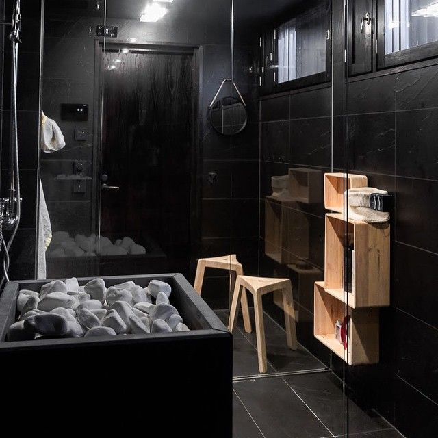 Tulikivi Rae sauna heater and white deco sauna stones in a stylish sauna with dark-tiled shower space.