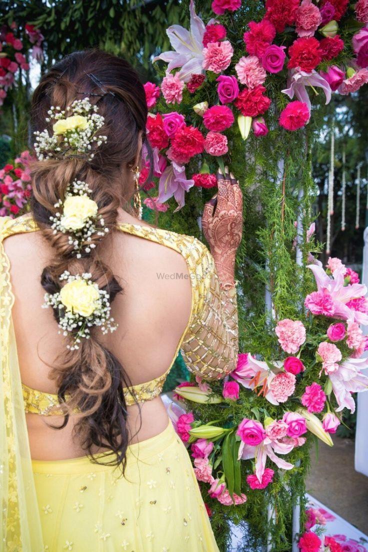 Mehendi Hairstyles - Yellow and Gold Mehendi Hairstyle with Floral Braid Hairstyle | WedMeGood #wedmegood #indianbride #indianwedding #bridalhairstyle #mehendihairstyle #yellow #backlessblouse