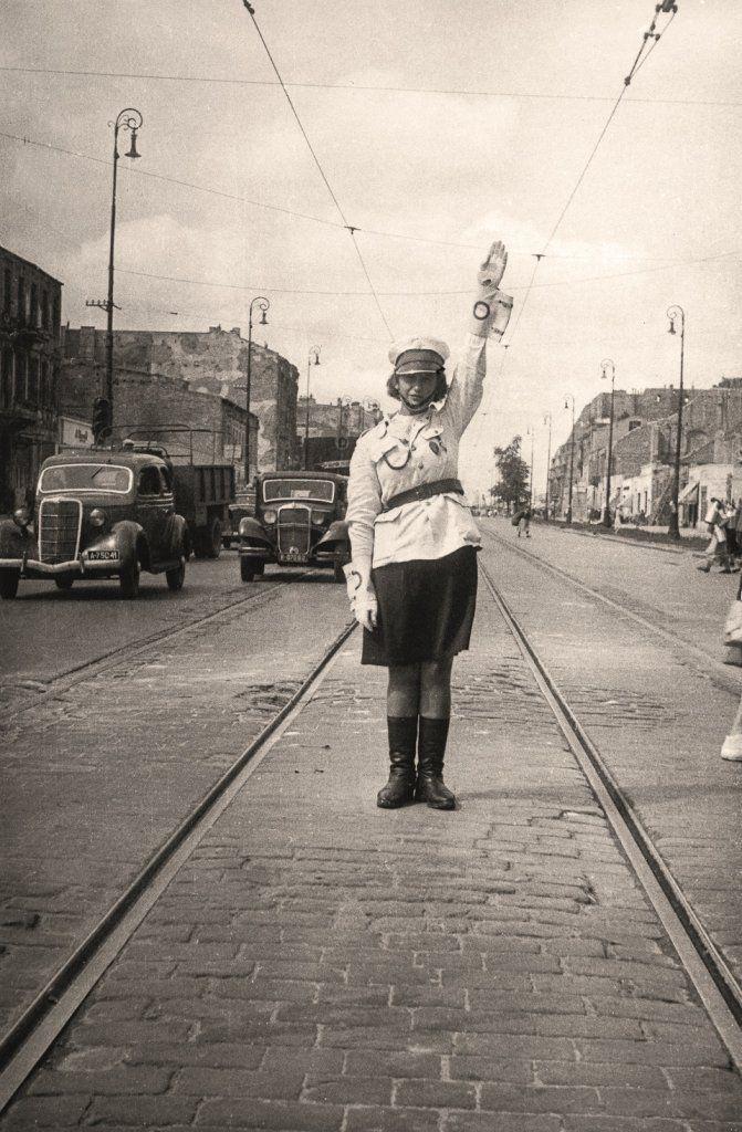 """""""Leokadia Krajewska - słynna Lodzia Milicjantka - jedna z pierwszych kobiet w Kompanii Ruchu Drogowego, kierowała ruchem na warszawskich skrzyżowaniach. Była niezwykle popularna, co skwapliwie wykorzystywała komunistyczna propaganda dla ocieplania wizerunku służb mundurowych. W 1948 roku na balu przodowników pracy Lodzia tańczyła pierwsze tango z premierem Józefem Cyrankiewiczem"""" - z podpisu pod zdjęciem w albumie """"Warszawa lata 40."""""""