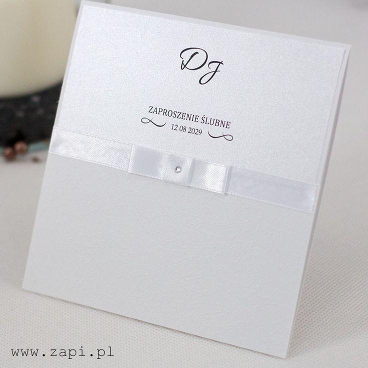 Eleganckie zaproszenie ślubne z satynową tasiemką i aplikacją. Kartka wykonana jest na białym tłoczonym papierze dekoracyjnym.