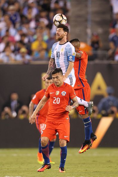 #COPA2016 #COPA100 Lionel Messi of Argentina heads the ball over Charles Aranguiz and Arturo Vidal of Chile during the championship match between Argentina and Chile at...