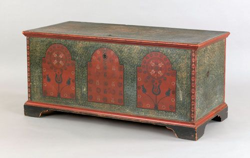 """Pennsylvania painted dower chest, ca. 1800, the front decorated with three red tombstone panels with tulip and potato stamp decoration on a green sponge ground supported by bracket feet, 23 3/4"""" h., 48 3/4"""" w. For a chest decorated by the same hand, see Stoudt, Early Pennsylvania Arts & Crafts, fig. 199."""
