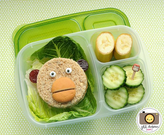 This was a really fun monkey easylunchbox. I placed some romaine lettuce in the larger compartment and put the monkey sandwich on top. The monkey sandwich was cut with my circle cutter, had fruit leather ears, icing eyes and a sliced nilla wafer mouth. The other compartments held a sliced banana (I start the peel from the bottom so Kirsten can peel it herself) and crinkle cut cucumbers with a cute monkey pick.