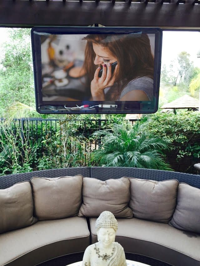 Awesome back porch with circular couch and The TV Shield weatherproof TV enclosure. #WeatherproofTV #Patio #Backyardideas #TheTVShield #OutdoorLiving