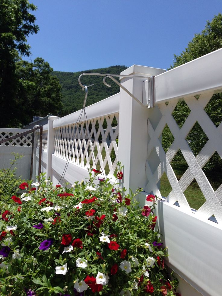 """DIY plant hanger for vinyl fence. Cost $5. Purchase aluminum bendable strip, cut 10"""" strip. Bend to fit fence and screw in hanger to strip. Cut ends of screws off and insert rubber pad to protect fence. Slide on fence."""