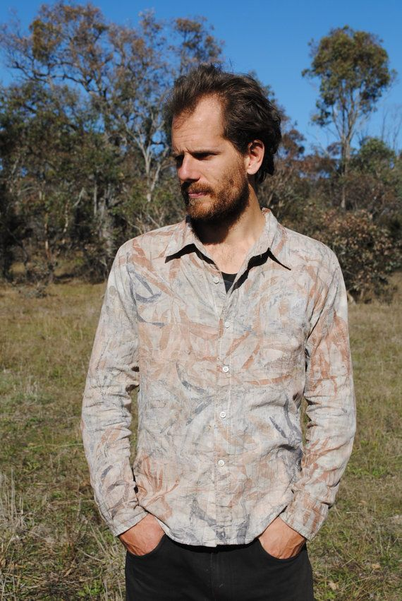 Up-cycled earthy mens cotton shirt eco-printed with a variety of eucalyptus leaves, gathered on Ngunnawal country in the ACT. The colour from the leaves has dyed this shirt a range of earthy oranges and greys. The shirt has elegant stitched lines and could be dressed up for a bush wedding or dressed down for a weekend bushwalk.  Size Small 53 cm underarm to underarm  Care instructions: To keep colours bright and fresh, wash in cold water and dry in the shade.