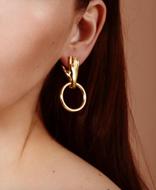 Cool unique earrings hand of gold holding on to the ear and a circle through the wrist