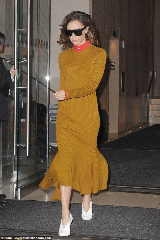 It mustard been love: Victoria Beckham wowed in a knitted dress with orange collar as she left her hotel in New York on Tuesday