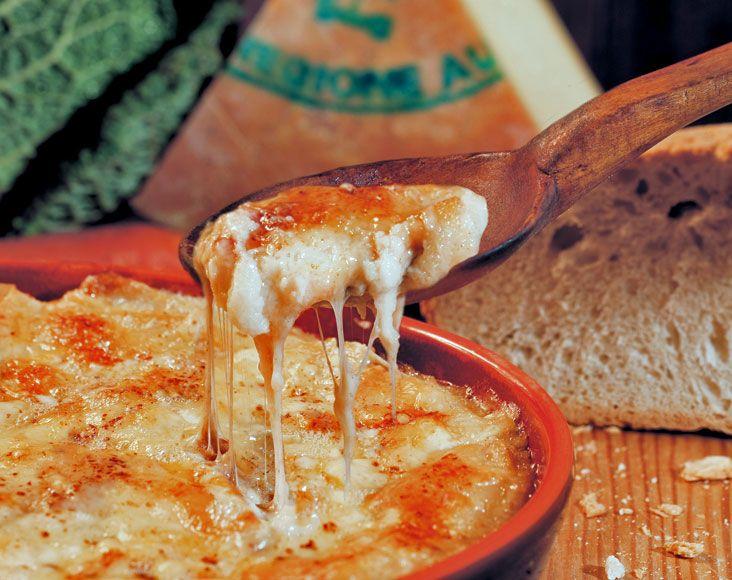 Valle d'Aosta - Seupa à la Vapelenentse. Occorrono pane raffermo e fontina - Ecco la ricetta DCO del Comune di Valpelline. Taglia del pane raffermo a fette di due cm. Imburra la teglia e copri con uno strato di pane. Taglia la fontina a fettine e forma un secondo strato. Ripeti l'operazione per tre volte. Copri l'ultimo strato con la fontina. Bagna con abbondante burro fuso con un pizzico di cannella e poi copri  con brodo di carne. Inforna fino a formare una crosticina dorata.