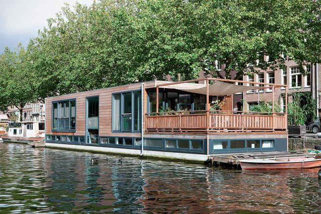 "A houseboat in Amsterdam incorporates large, low windows that provide expansive watery perspectives and rippling reflections. ""In designing this houseboat, I tried to ensure that you experience the water as much as possible,"" says architect David Keuring.  Photo by: Rene Mesman"
