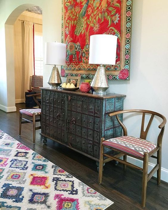 Eclectic mix of furniture in this colorful foyer - love the colorful tapestry…
