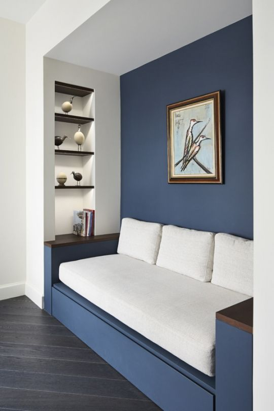 House tour: a bright and modern Paris apartment: Plush linen upholstered seating finds a home against a bold blue wall, a key colour throughout the space.