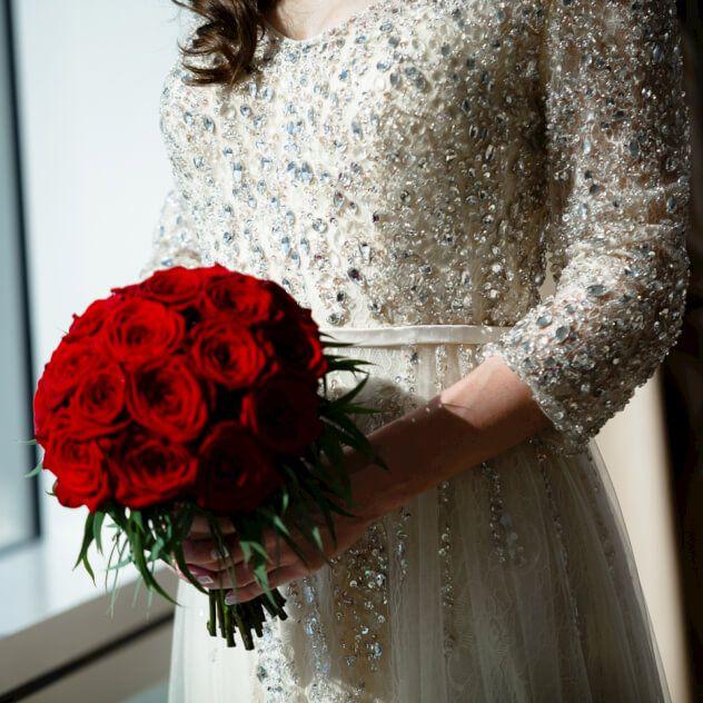 Свадебный букет из красных роз в классическом исполнении с добавлением эвкалипта сорта Николи, который имеет серебристо-зеленый оттенок, выгодно подчеркивающий истинно красный цвет сортовых роз Ред Наоми. Этот универсальный состав букета будет исключительным акцентом как для свадебного наряда в классическом стиле, так и для экстравагантного образа. Дополнительно возможно исполнение бутоньерки - 400 руб.
