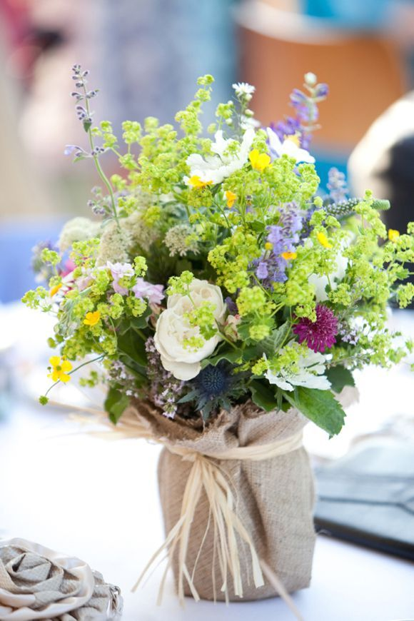 pretty country garden / wildflower bunches in vases wrapped in hessian / burlap and tied with raffia