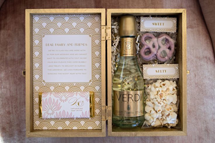 Your guests will swoon over this amazing welcome basket - filled with a little something sweet, something salty, and a bottle of bubbly.   Photographer:  Carla Ten Eyck Photography