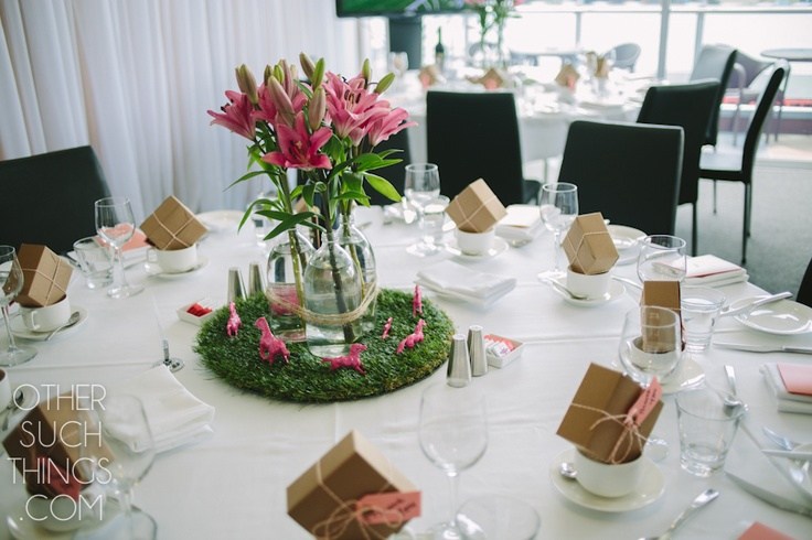 Table setting of faux grass, lilies and pink ponies. Melbourne Cup Luncheon at Majestic Roof Garden Hotel.