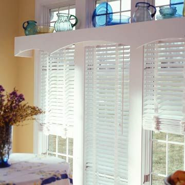 For a clean, contemporary look, try outfitting multiple windows with identical wood slat blinds -- or mini-blinds. Top the trio with a curved-edge cornice for unifying touch that also becomes display space.
