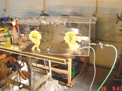 """Titanium Welding Chamber by Ed Haas -- Homemade titanium welding chamber adapted from a surplus terrarium and intended to provide the necessary sealed, inert gas environment. 4"""" holes were cut in the plexiglass to accommodate rubber gloves and another hole was drilled on the end for the argon gas inlet. http://www.homemadetools.net/homemade-titanium-welding-chamber"""
