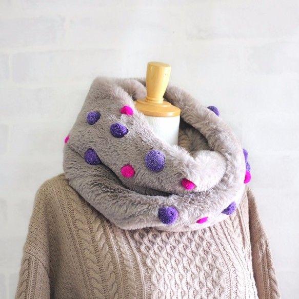 ★ふわふわもこもこの毛並みが暖かなフェイクファーで作ったスヌード。手触り抜群のなめらかな素材です。ねじれスヌードなのでそのままスポッとかぶるだけでサマになります。グレージュ色のファーにピンクとパープルの大小のポンポンをランダムに付けてカラフルでユニークなアクセントに。暗めのコーディネートになりがちな冬のファッションを明るくしてくれます。ボリュームのあるファースヌードはとても暖かで重宝しそう。クリスマスプレゼントにもオススメです。【サイズ】幅約23cm 長さ(一周)約75cm 【素材】ポリエステル100%【お手入れ方法】中性洗剤でやさしく手洗いをお薦め致します。『冬支度ハンドメイド2017』