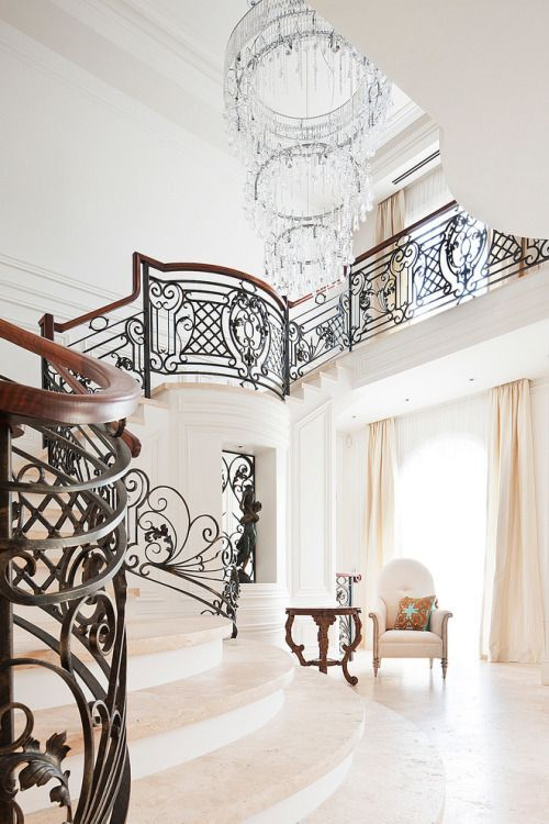 Beautiful wrought iron stair railing and awesome chandelier in this stairway