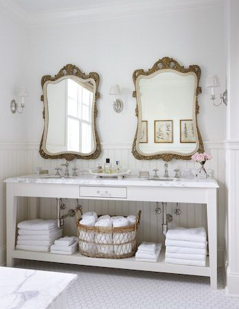 Open bathroom vanity with statement vintage mirrors.