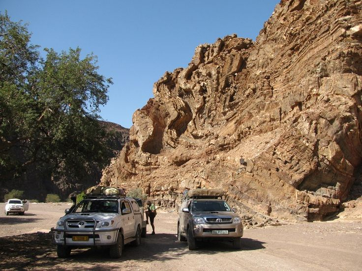 Hans en Herbie gedenkplaat n Foto van die Hans-en-Herbie-kloof waar die gedenkteken teen die rotswand sigbaar is, regs bo die regterhandse voertuig.