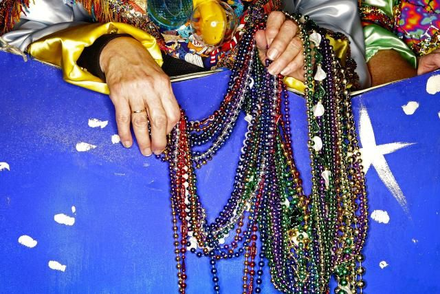 What Is Fat Tuesday?: Ruby Gallagos holds a handful of beads before the start of the Excalibur Mardi Gras parade February 17, 2006, in Metairie, Louisiana.
