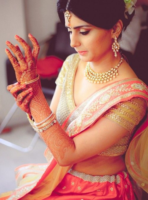 Indian bride wearing bridal lehenga and blouse. Bridal jewellery. Necklace and earrings