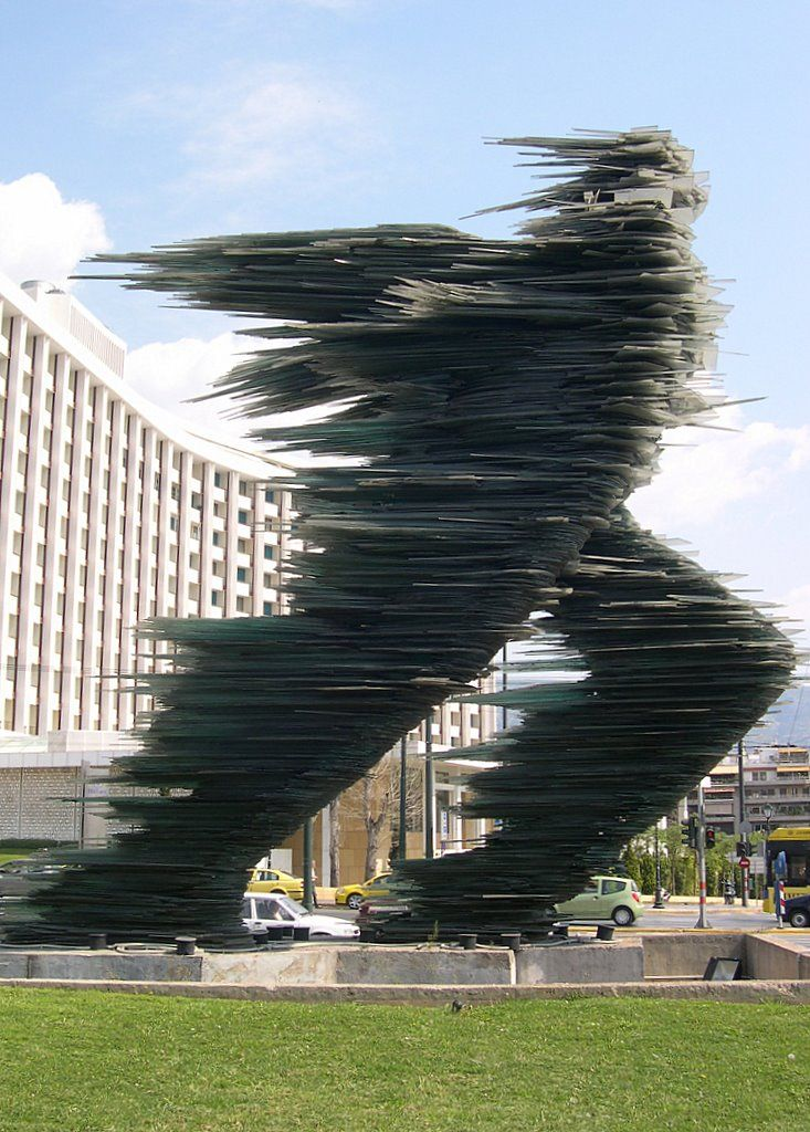"Costas Varotsos "" The Runner"" – in Athens The legendary sculpture ""The Runner"" is located in Athens since 1988. It is made entirely of dark green glass. The author of this unusual sculpture is the Greek sculptor COSTAS VAROTSOS."
