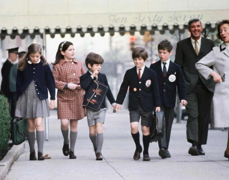 Dressed in school uniforms, Caroline Kennedy (l.) and her little brother JFK Jr. return home from school in this photo, shot in 1968. The family moved to Manhattan following President Kennedy's assassination five years earlier.