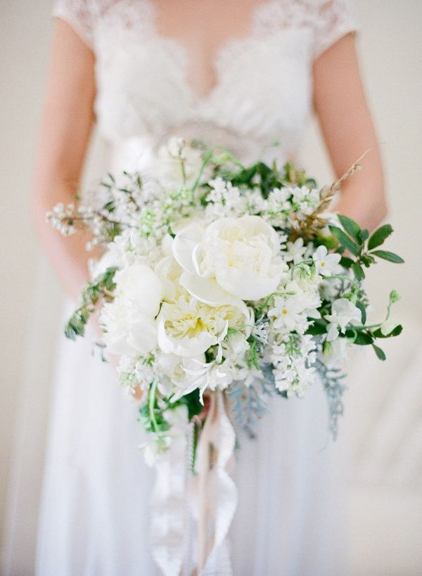 The bridal bouquet will be a loose clutch of cream hydrangeas, white peonies, white lilacs, white ranunculus, jasmine vine, and camellia foliage wrapped in ivory ribbon similar to this image...
